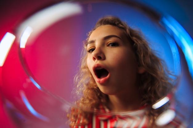 Verrast jonge vrouw in feestkleding poseren met glas wijn. emotioneel vrouwelijk schattig gezicht. uitzicht vanuit het glas