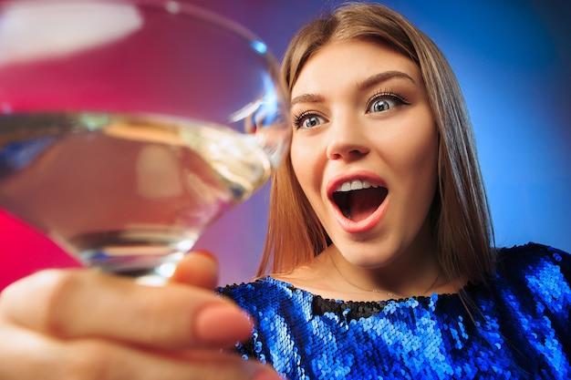 Verrast jonge vrouw in feestkleding poseren met glas wijn. emotioneel vrouwelijk schattig gezicht.