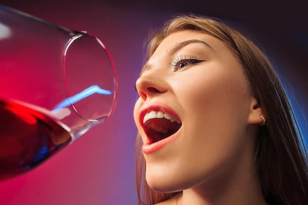 Verrast jonge vrouw in feestkleding poseren met glas wijn