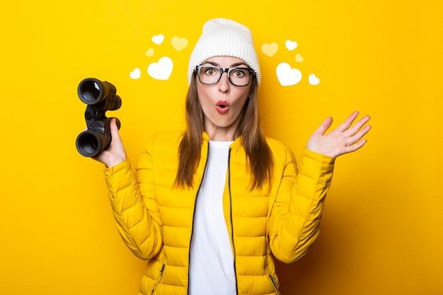 Verrast jonge vrouw in geel jasje met verrekijker op gele muur.