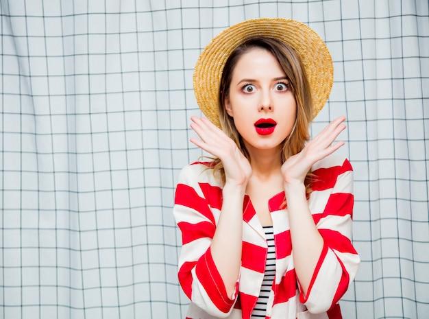 Verrast jonge vrouw in hoed en gestreepte jas