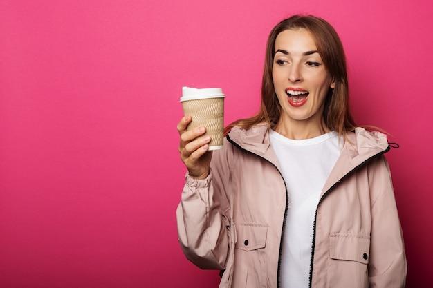 Verrast jonge vrouw in jasje met papieren beker op roze oppervlak