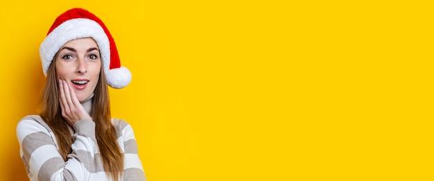 Verrast jonge vrouw in kerstman hoed op een gele achtergrond. banier.