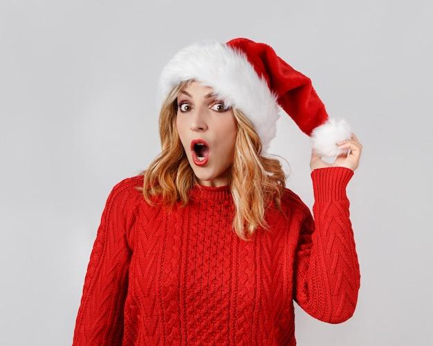 Verrast jonge vrouw in kerstmishoed wat betreft hoed