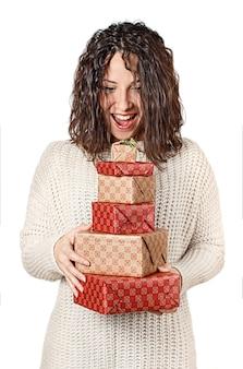 Verrast jonge vrouw in trui met geschenken in handen