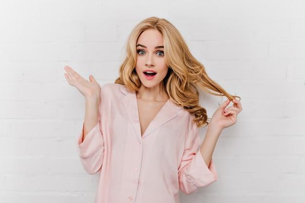 Verrast jonge vrouw in zijden pyjama speelt met haar golvende haren. blond meisje in nachtkostuum verbazing uiten dichtbij dichtgemetselde muur.