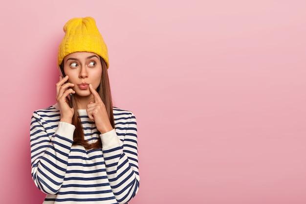 Verrast jonge vrouw kijkt verrassend opzij, houdt mobiele telefoon in de buurt van oor, voert telefoongesprek, kijkt weg, draagt modieuze outfit