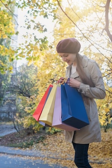 Verrast jonge vrouw met boodschappentassen in handen. herfst promotie. verticaal kader.
