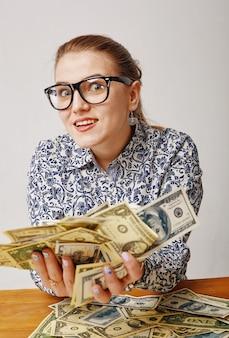 Verrast jonge vrouw met dollars in haar handen