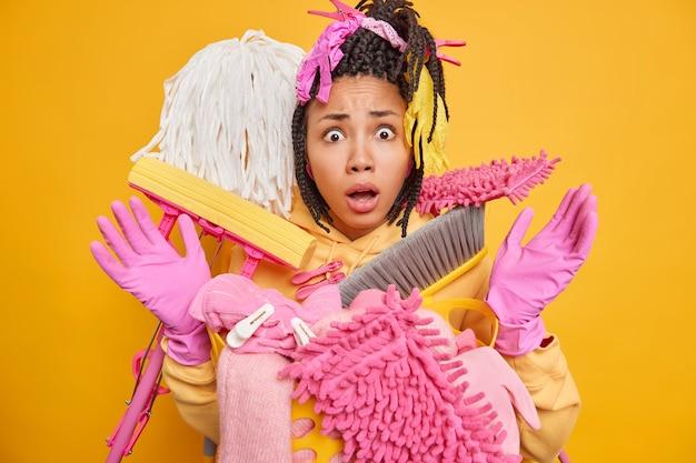 Verrast jonge vrouw met donkere huid en dreadlocks poseert in de buurt van een emmer vol schoonmaakspullen