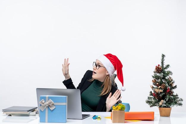 Verrast jonge vrouw met kerstman hoed en bril zittend aan een tafel met een kerstboom en een cadeau erop op witte achtergrond