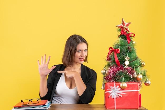 Verrast jonge vrouw met vijf in pak in de buurt van versierde kerstboom op kantoor op geel