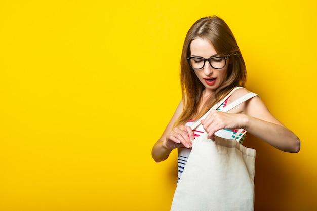 Verrast jonge vrouw op zoek naar linnen tas met aankopen op gele achtergrond.