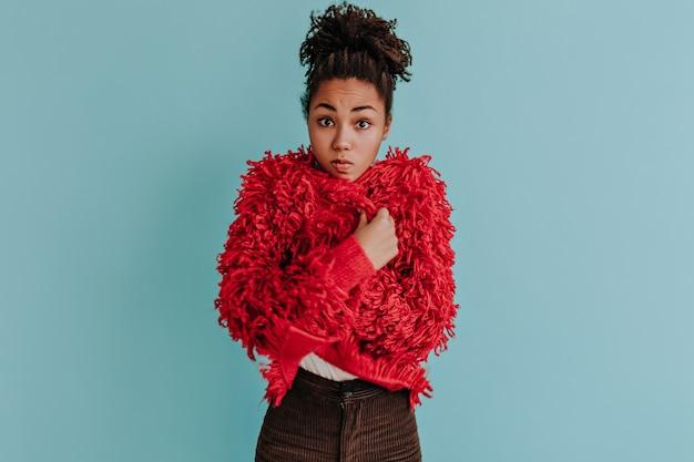 Verrast jonge vrouw poseren in rode eco jas