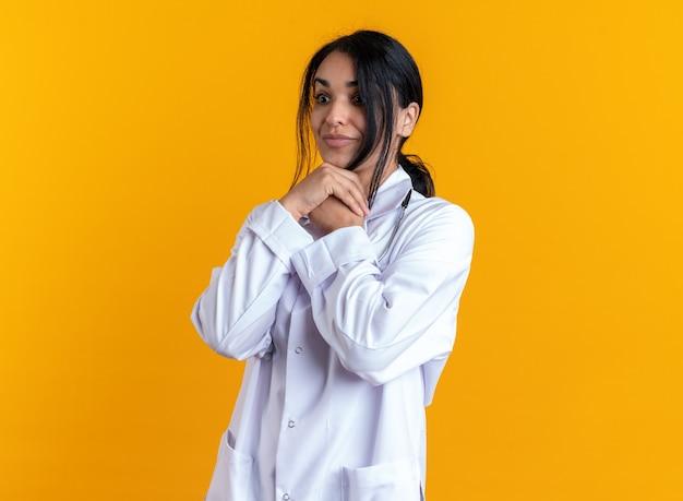 Verrast jonge vrouwelijke arts die een medisch gewaad draagt met een stethoscoop die handen onder de kin legt die op gele achtergrond wordt geïsoleerd