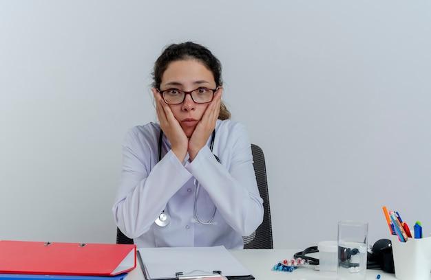 Verrast jonge vrouwelijke arts die medische mantel en stethoscoop en bril draagt die aan bureau met medische hulpmiddelen zit die het houden van handen op geïsoleerd gezicht kijkt