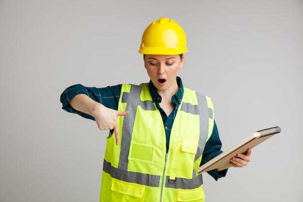 Verrast jonge vrouwelijke bouwvakker die veiligheidshelm en veiligheidsvest draagt ?? die blocnote houdt die en naar beneden wijst