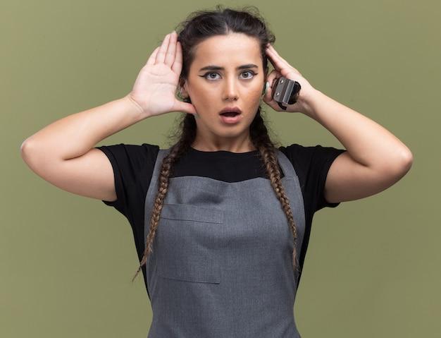 Verrast jonge vrouwelijke kapper in uniform houden van tondeuses handen op het hoofd zetten geïsoleerd op olijfgroene muur