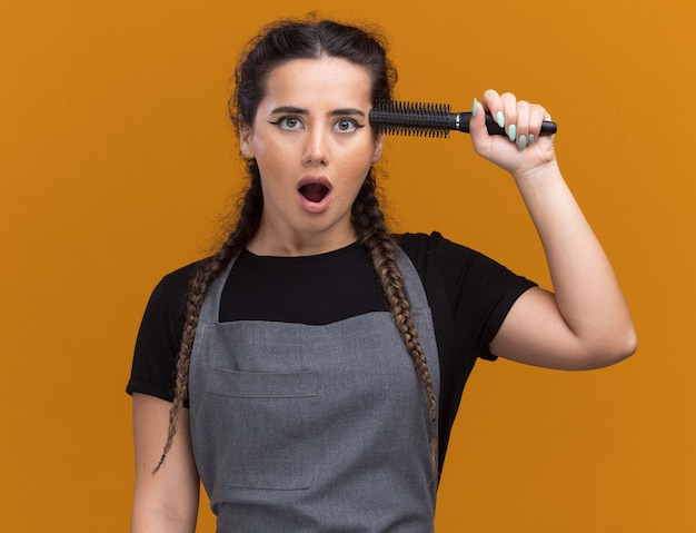 Verrast jonge vrouwelijke kapper in uniform kam zetten tempel geïsoleerd op oranje muur