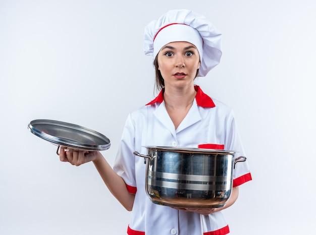 Verrast jonge vrouwelijke kok dragen chef uniform holding steelpan met deksel geïsoleerd op een witte achtergrond