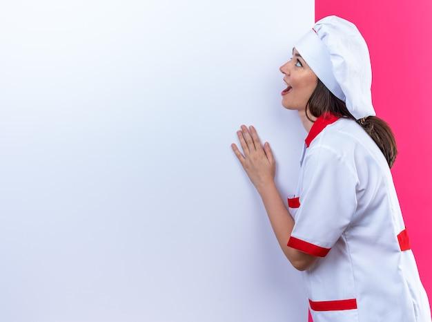 Verrast jonge vrouwelijke kok met chef-kok uniform staat in de buurt van witte muur geïsoleerd op roze muur met kopieerruimte