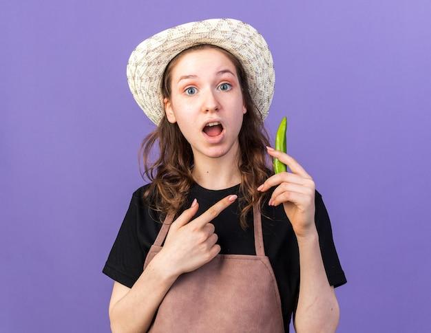 Verrast jonge vrouwelijke tuinman die een tuinhoed draagt en naar peper wijst