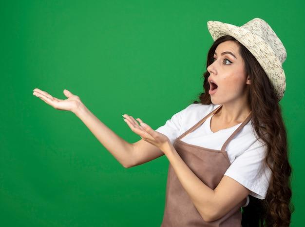 Verrast jonge vrouwelijke tuinman in uniform dragen tuinieren hoed kijkt en wijst naar kant geïsoleerd op groene muur