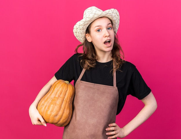 Verrast jonge vrouwelijke tuinman met een tuinhoed met pompoen die de hand op de heup zet, geïsoleerd op een roze muur