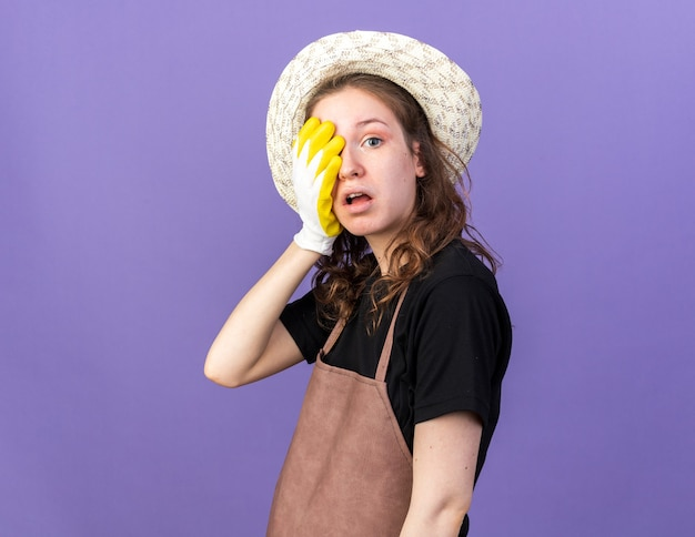 Verrast jonge vrouwelijke tuinman met tuinhoed met handschoenen bedekt gezicht met hand geïsoleerd op blauwe muur
