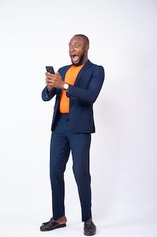 Verrast jonge zakenman vieren terwijl hij naar zijn telefoon kijkt