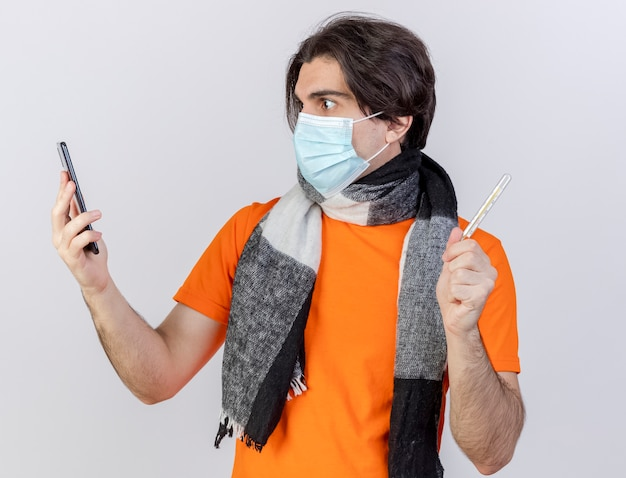 Verrast jonge zieke man met sjaal en medische masker houden thermometer kijken naar telefoon in zijn hand geïsoleerd op een witte achtergrond
