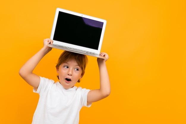 Verrast jongen houdt een laptop op zijn hoofd op een gele muur met kopie ruimte