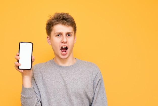 Verrast jongen op een gele heeft een smartphone met een wit scherm en kijkt in de camera