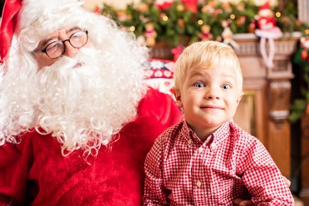 Verrast jongen zittend op de benen van santa