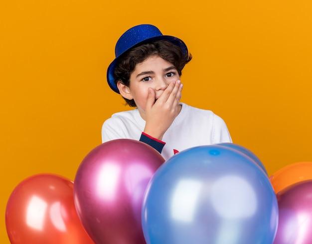 Verrast jongetje met een blauwe feestmuts die achter ballonnen staat en zijn mond bedekt met hand
