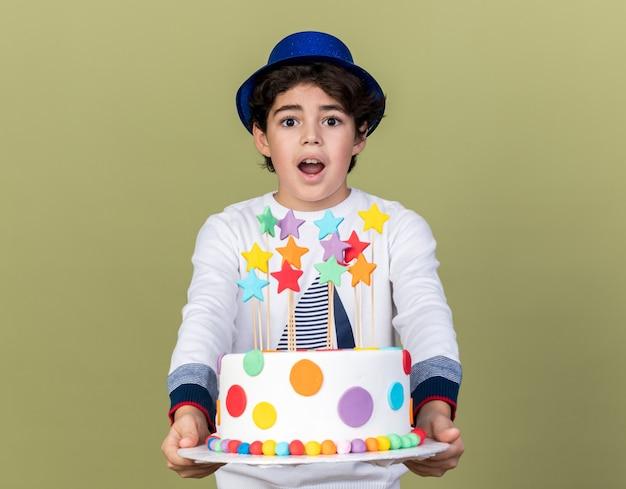Verrast jongetje met een blauwe feestmuts die cake voor de camera vasthoudt