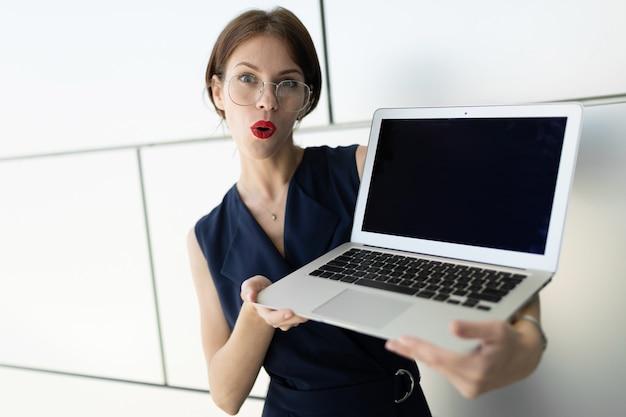 Verrast kantoor werknemer meisje met rode lippen met een leeg notebook scherm leeg kijkt verbaasd naar de camera