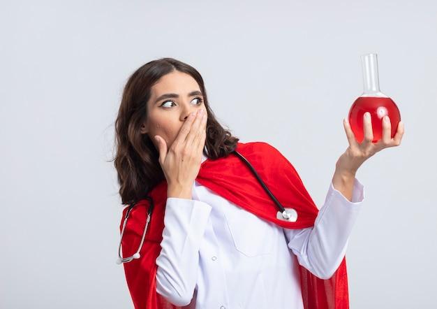 Verrast kaukasisch superheldmeisje in doktersuniform met rode cape en stethoscoop legt hand op mond houden en kijken naar rode chemische vloeistof in glazen kolf op witte muur