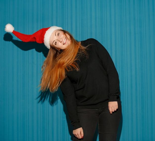 Verrast kerstmismeisje dat een kerstmuts draagt op de blauwe studioachtergrond