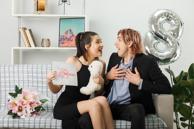 Verrast kijken naar elkaar jong koppel op gelukkige vrouwendag met teddybeer en wenskaart man handen op hart zittend op de bank in de woonkamer