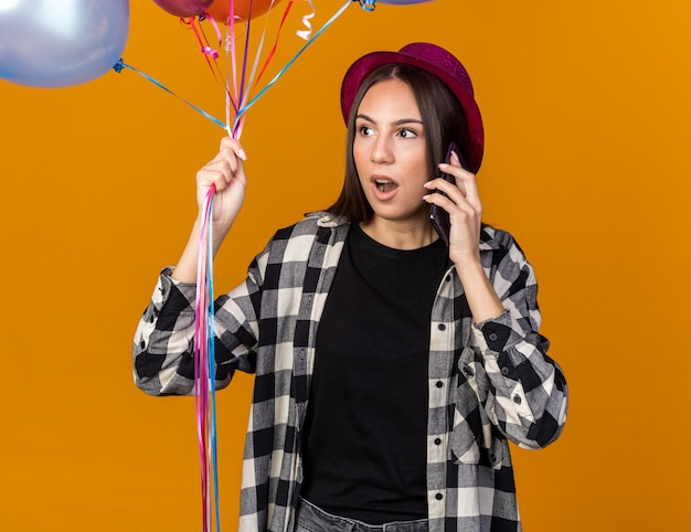 Verrast kijkend naar een jong mooi meisje met een feestmuts en ballonnen met ballonnen spreekt op de telefoon