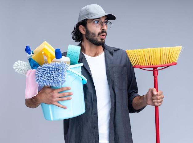Verrast kijkend naar kant jonge knappe schoonmaakster die t-shirt en pet draagt ?? die emmer met schoonmaakgereedschap met dweil houdt geïsoleerd op een witte muur