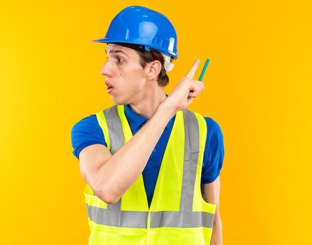 Verrast kijkende jonge bouwer man in uniform met potlood en wijst naar achter geïsoleerd op gele muur met kopieerruimte