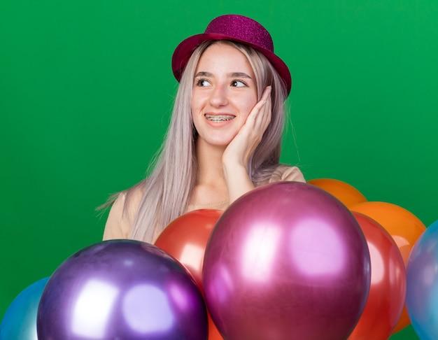 Verrast kijkende jonge, mooie meid met een feesthoed en beugels die achter ballonnen staan en de hand op de wang leggen