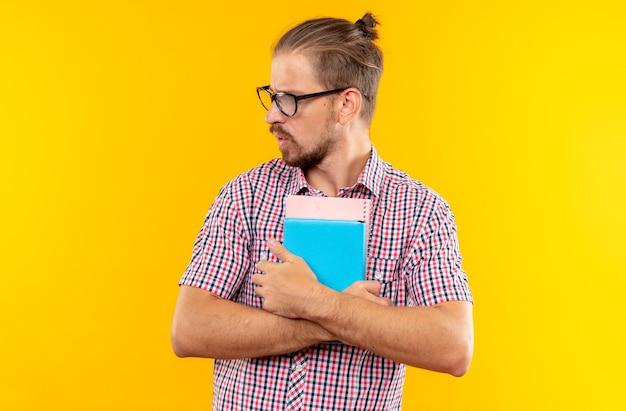 Verrast kijkende jonge student die een rugzak draagt met een bril die een boek vasthoudt