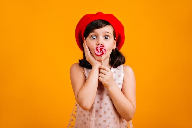 Verrast kind lolly eten. geschokt preteen meisje met snoep geïsoleerd op gele muur.