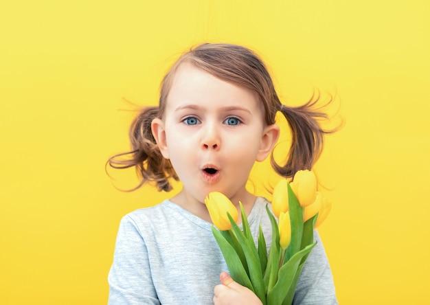 Verrast kind meisje in grijze jurk houdt tulpen op een gele achtergrond