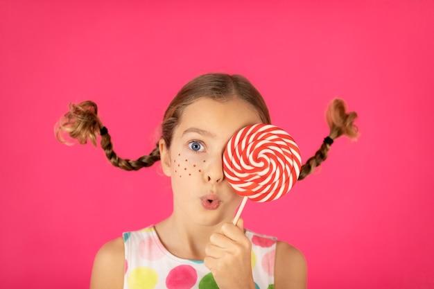 Verrast kind met vlechten die lolly houden portret van buitensporig meisje tegen roze background