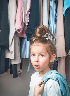 Verrast kind op de achtergrond van dingen die op een hanger hangen. zijaanzicht.