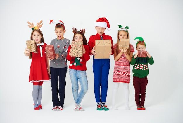 Verrast kinderen kijken naar hun kerstcadeautje